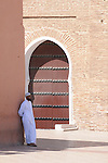 A man stands in the shade in front of the Koutoubia Mosque in Marrakesh, Morocco...