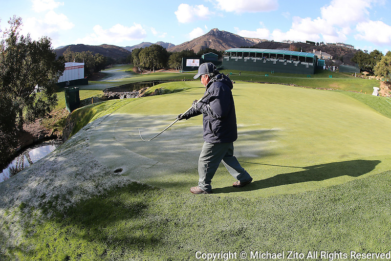 12/06/13 Thousand Oaks, CA:  A grounds keeper whisks frost off the 18th green delaying the start of the second round of the 2013 Northwestern Mutual World Challenge, benefitting the Tiger Woods Foundation.