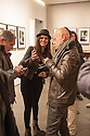 Fans of Andy Summers, former guitar player of the Police, writer and photographer, show each others the pitcures taken by smartphone of their idol at Leica Gallery in Milan, March 22, 2016. At Leica Gallery there is an exhibition of photographs by Andy Summers.