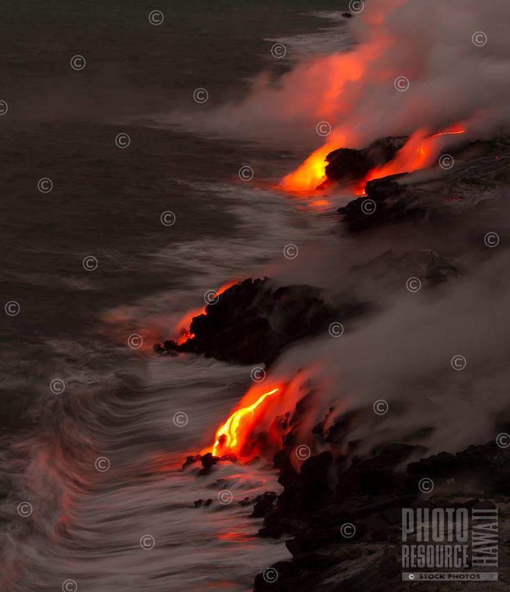 Active lava meets crashing waves on the coastline along Kalapana and Hawai'i Volcanoes National Park, Big Island, Hawaii.