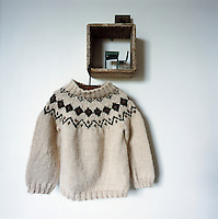 A child's knitted fair isle jumper hangs from a wooden box fixed on the wall.