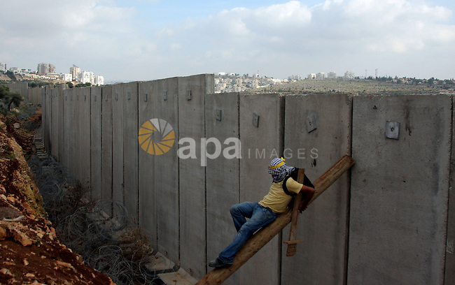 Palestinian demonstrator climbs on a part of the wall of Israel's separation barrier during a protest against Israel's controversial separation barrier in the West Bank village of Nilin, near the city of Ramallah, Friday, Jan. 1, 2010. Photo by Issam Rimawi