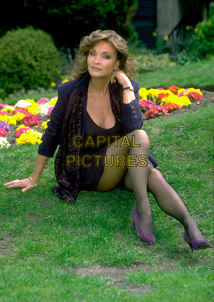 KATE O'MARA.Photocall, London, England, .17th April 1996..full length legs sitting on grass black tights jacket dress mini short skirt.CAP/CS.©Capital Pictures