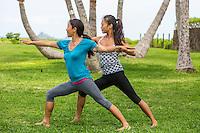 Yoga instructor Miki Sato assists a student with yoga asana at beach park on O'ahu.