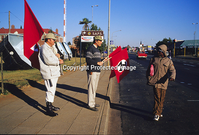 DIPOAFR000100.Politics, Right wing. man, white, black, uniform, politcs, racist, racism, men, park,.two unidentified members of AWB, a right wing movement, walks with their flags in central Potchefstrom, South Africa, as a black man walks by..©Per-Anders Pettersson/iAfrika Photos