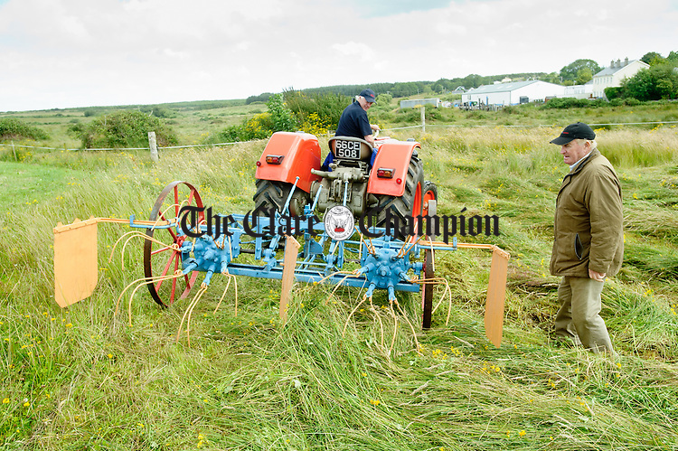 Cooraclare's Joe Lillis shaking hay with a vintage machine on a 1966 Zetor 4011 watched by martin Moloney of Kilmaley during the field day as part of the Festival of Fun in Kilmihil. Photograph by John Kelly.