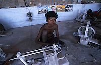 INDIA Tamil Nadu, Karur, child labour, boy work in a polishing unit for artificial synthetic gems, he is polishing the stones fixed with wax on bamboo sticks / INDIEN, Kinderarbeit, Junge arbeitet in einer kleinen Edelsteinschleiferei im Dorf V. Pudur bei Karur, hier werden Halbedelsteine und kuenstliche Edelsteine poliert