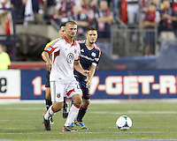 D.C. United midfielder Perry Kitchen (23) passes back to goalkeeper. New England Revolution midfielder Kelyn Rowe (11). In a Major League Soccer (MLS) match, the New England Revolution (blue) defeated D.C. United (white), 2-1, at Gillette Stadium on September 21, 2013.