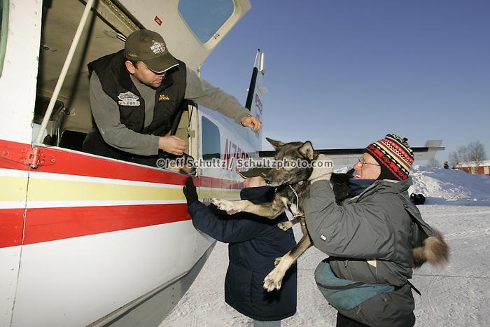 "Volunteers help ""Caravan Joe"" load dropped dogs onto the Penair Caravan on Wednesday morning at the Nikolai checkpoint.  2005 Iditarod Trail Sled Dog Race."