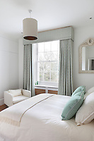 A white guest bedroom with furnishings in complimentary shades of green and cream