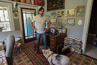 NWA Democrat-Gazette/J.T. WAMPLER  James Moore with Emelia the house pig in his home office in his 1936 Craftsman-style farmhouse in Huntsville.