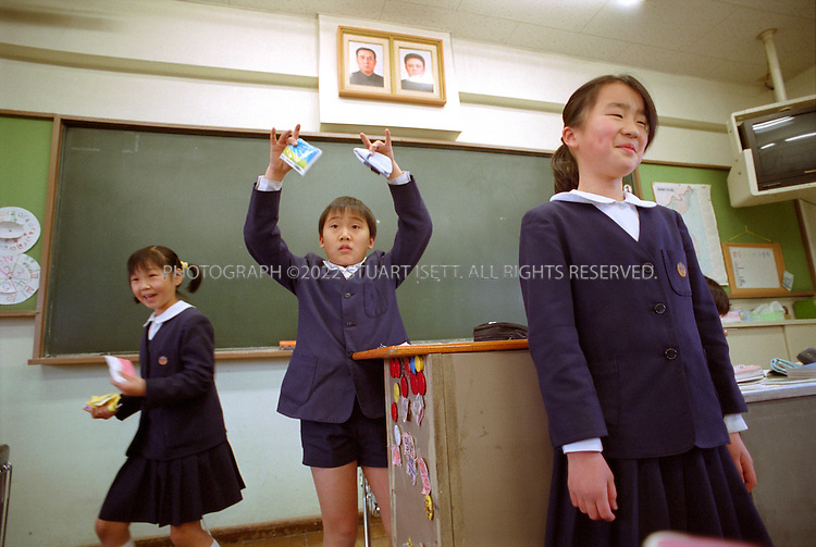 1/17/2002--Tokyo, Japan..Students hodl a presentation in class at the Tokyo-Korean 1st Elementary and Middle School, a school for North Korean residents in Japan in Tokyo's Arakawa ward on the north side of the city. Above the blackboard are two photographs of Korean leaders Kim Il Sung and Kim Jong Il....All photographs ©2003 Stuart Isett.All rights reserved.This image may not be reproduced without expressed written permission from Stuart Isett.