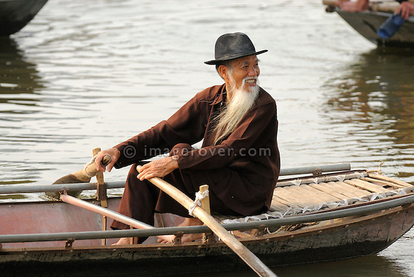 Asia, Vietnam, Tam Coc near Ninh Binh. Elderly vietnamese boat man at Tam Coc (Three Caves). To visit the Three Caves (Tam Coc) tourists are punted in metal boats along the watery landscape and through three long caves. At some places these are so low that peope have to duck, while boat people propel the boat by pushing on the cave roof with their hands.