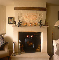 A country sitting room decorated in neutral tones. A woodburner sits in a stone fireplace with a chimney breast with a wood lintel. Lit tealights and cherubs are arranged on a mantelpiece.