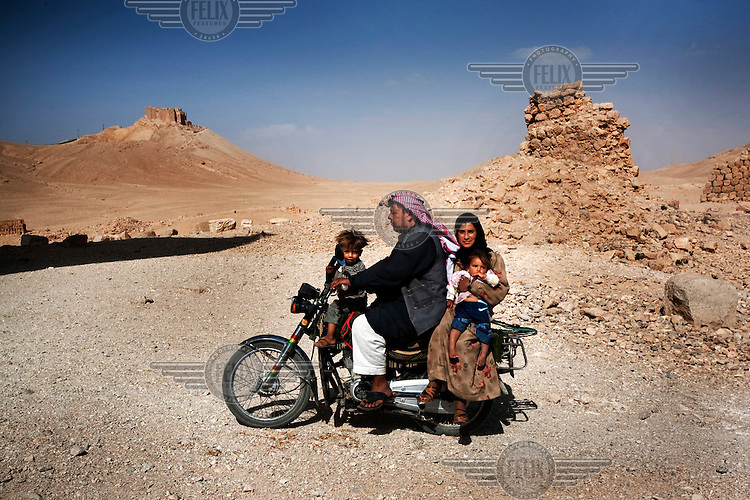 A man with his family drives a scooter near Palmyra. The World Heritage Site of Tadmor (Palmyra) is mentioned in documents from the 2nd millennium BC. It was a town that grew rich from the caravan trade, and made history as the captial of the rebelious Queen Zenobia, who was eventually subdued by the Romans. In the foreground are the Roman ruins of Baal Temple, and in the background, the 17th Century Arab fortress of Qalaat Ibn Maan.