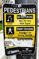 Street signage on traffic lights in Toronto, Ontario.