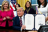 US President Donald J. Trump (C) holds up 'the Women's Suffrage Centennial Commemorative Coin Act', after signing it during a ceremony, beside United States Senator Marsha Blackburn (Republican of Tennessee) (L), in the Oval Office of the White House in Washington, DC, USA, 25 November 2019. Trump signed 'H.R. 2423, the Women's Suffrage Centennial Commemorative Coin Act' - a bill directing the US Treasury to mint and issue up to four hundred thousand one-dollar silver coins honoring women that played a role in gathering support for the 19th Amendment.<br /> Credit: Michael Reynolds / Pool via CNP