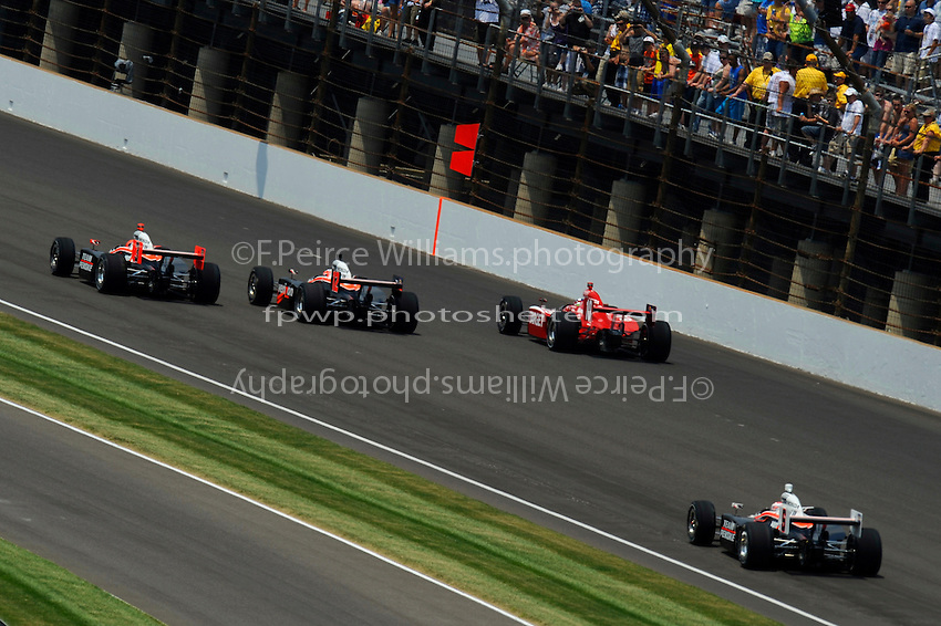 The 3 Penske cars, Helio Castroneves (#3), Will Power (#12) & Ryan Briscoe (#6), that were expected to dominate the race and the one car that did, Dario Franchitti (#10) as they roll through turn 3 and to the green flag.