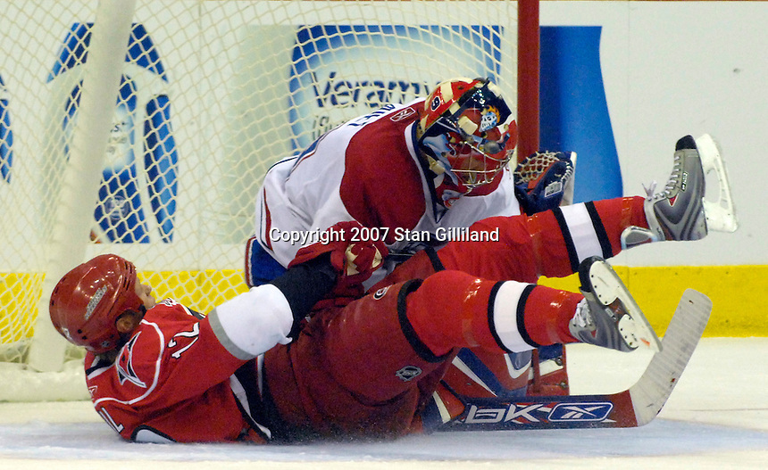 Carolina Hurricanes' Eric Staal (12) slides into Montreal Canadiens' goalie Cristobal Huet after being tripped during their game Friday, Oct. 26, 2007 in Raleigh, NC. The Canadiens won 7-4.