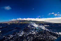 Wave breaking in wake of sailboat in the Pailolo Channel off Molokai, Hawaii
