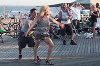 An oblivious man and woman dance on Coney Island Boardwalk in New York city borough of Brooklyn, Sunday July 31, 2011. Built in 1923 and officially named The Riegelmann Boardwalk, Coney Island Boardwalk is located along the southern shore of the Coney Island peninsula adjacent to the Atlantic Ocean.