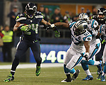 Seattle Seahawks Marshawn Lynch (24) runs through the Carolina Panthers defenders Luke Kuechly (59) and Thomas Davis (58) enroute to a 25-yard gain in the NFC Western Division Playoffs at CenturyLink Field  on January 10, 2015 in Seattle, Washington. The Seahawks beat the Panthers 31-17. ©2015. Jim Bryant Photo. All Rights Reserved.