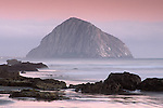 Evening light over Morro Rock, ocean waves, and fog from Morro Strand State Beach, near Morro Bay, California