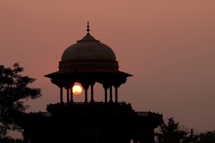 A setting sun peeks through an opening in a domed structure on the periphery of the Taj Mahal complex.