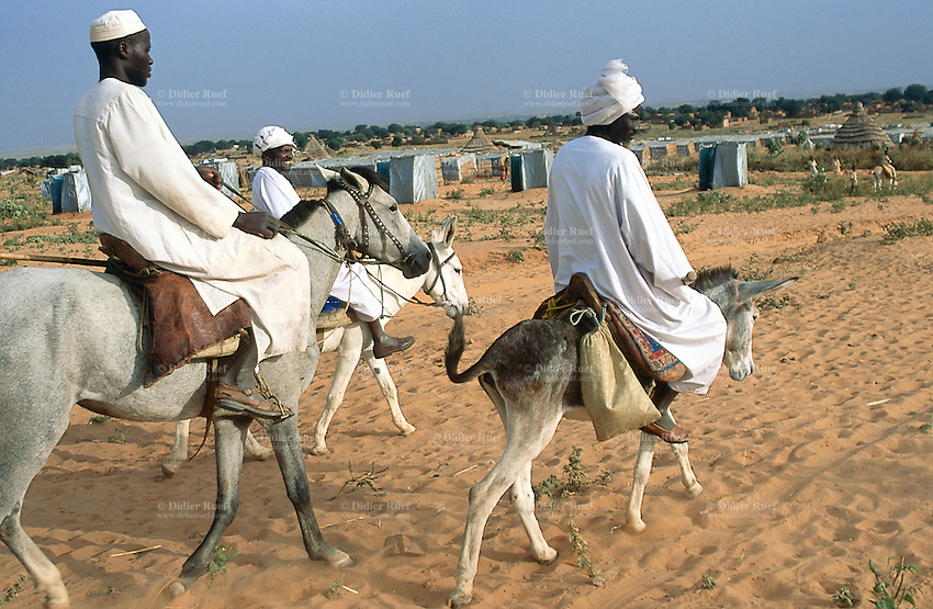 Sudan. West Darfur. Ryiadh. Ryiadh is located on the outskirts of the town of Al Geneina and is a camp for internally displaced people (IDP)) from the civil war. A group of men, dressed in white clothes and a turban on the heads, ride horses and donkeys and cross Ryiadh camp. © 2004 Didier Ruef