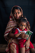 20 year old Mamta Devi poses for a portrait with her 23 months old son, Rohit Raut at the government health centre in Hanuman Nagar in Saptari, Nepal.