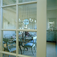 The elegant dining room is glimpsed through the glass panes of the double doors