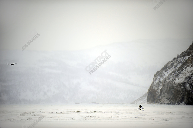 A man cycled over the frozen sea off Magadan after fishing on a Sunday morning. Russia, February 5, 2011