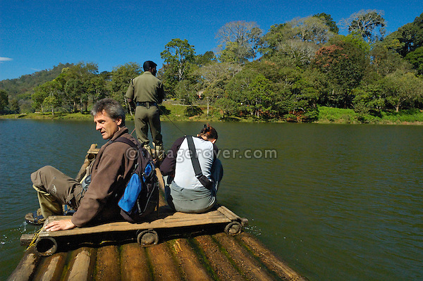 India, Kerala, Periyar/Kumily, Periyar Tiger Reserve.  Two western tourists in the Periyar Tiger Reserve crossing the Periyar Lake by raft with their local indian guide. Periyar /  Kumily, Kerala, India. No releases available.