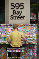 Toronto (ON) CANADA - July 2012 - A stranger play the piano  in downtown Toronto . ..These pianos scattered around the city are loans from various countries that will take part in the 2015 Pan American games..