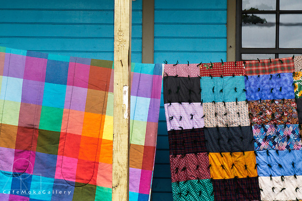 Colourful fabric bedspreads hanging out to dry on a turquoise wooden porch