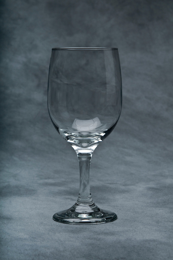 Empty cup of glass for wine over gray textured background.
