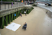 A Roma trumpet player busking on the south bank of the river Thames, London ,watched by his wife and daughter.