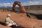 Older woman relaxing at Delicate Arch in Arches National Park, Moab, Utah, USA. .  John offers private photo tours in Arches National Park and throughout Utah and Colorado. Year-round.