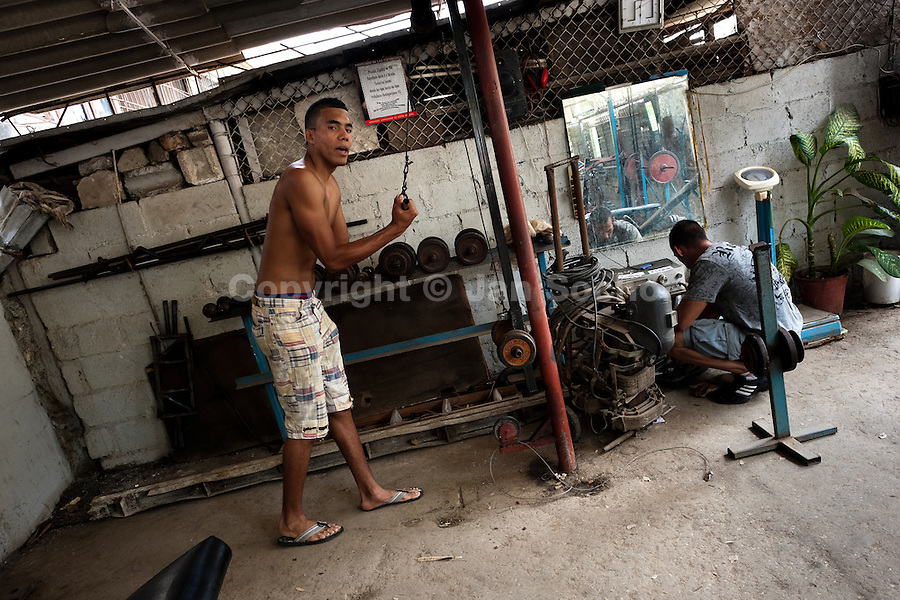 A young Cuban man does fitness exercise with barbells at a bodybuilding gym in Alamar, a public housing complex in the Eastern Havana, Cuba, 9 February 2011.