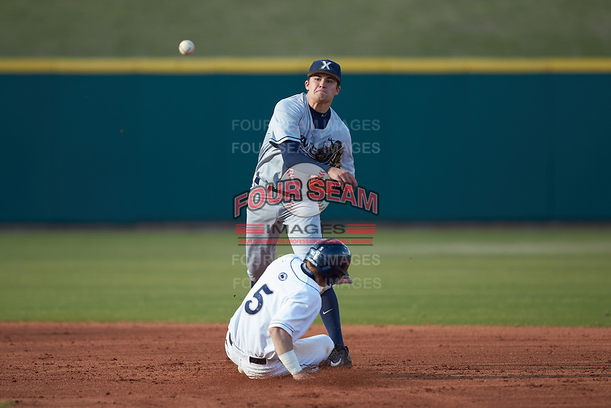 Conor Grammes (4) of the Xavier Musketeers makes a throw to first base against the while Joe Weisenseel (5) of the Penn State Nittany Lions slides into second base at Coleman Field at the USA Baseball National Training Center on February 25, 2017 in Cary, North Carolina. The Musketeers defeated the Nittany Lions 7-5 in game two of a double header. (Brian Westerholt/Four Seam Images)