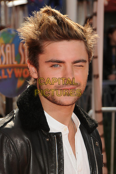 "Zac Efron.'Dr. Suess' ""The Lorax"" L.A. Premiere held at The Universal City Walk Theatre in Universal, Los Angeles, California, USA..February 19th, 2012.headshot portrait white stubble facial hair black leather jacket eye closed wink winking blink blinking .CAP/ADM/BP.©Byron Purvis/AdMedia/Capital Pictures."