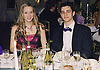 Teenage couple sitting at dinner table wearing black tie and ball gown,