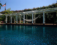 The white pillars of the arbour reflect in the shimmering blue waters of the swimming pool