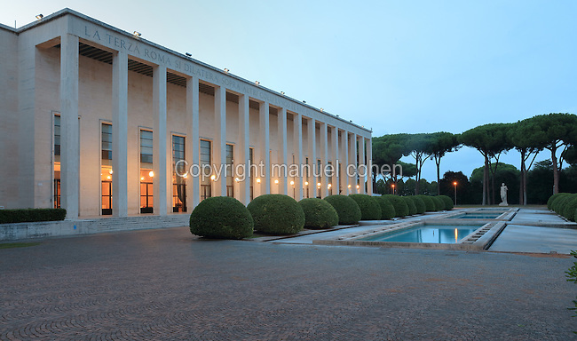 Palazzo degli Uffici, headquarters of EUR SpA, built 1937-39 in Fascist style, designed by Gaetano Minnucci, 1896-1980, and built as part of the EUR or Expositione Universale di Roma (Rome Universal Exhibition), planned by Marcello Piacentini, Rome, Italy. The exhibition was to take place in 1942 to celebrate the 20th anniversary of the fascist regime. Fascist architecture developed in the late 1920s and 1930s, as a modernist style in times of nationalism and totalitarianism under Benito Mussolini. It is characterised by large, square, symmetrical buildings with little or no decoration, often inspired by ancient Rome and designed to convey strength and power. Picture by Manuel Cohen