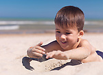 Happy smiling cute little boy playing with sand at the beach. Three year old child. Lake Huron, Ontario, Canada.