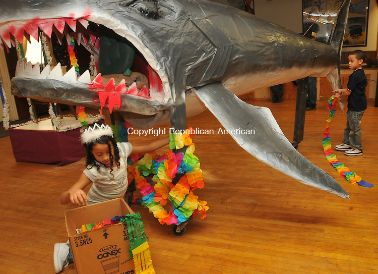 WATERBURY, CT- 13 February 2010 - 021310IP10- Erica Soares, 9, and her brother Jose Carlos Soares, of Waterbury, decorate the base of a shark that is the centerpiece display of the 18th annual Carnival party at Cape Verde Club in Waterbury on Saturday. They were decorating before the evening party started. The shark was made out of paper mache, wood and a table by Waterbury residents Adam Soares and Sylvester Degraca. <br /> Irena Pastorello Republican-American