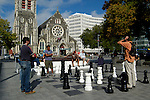 Playing outdoor chess in Cathedral Square with Christchurch Cathedral in the background, Christchurch New Zealand