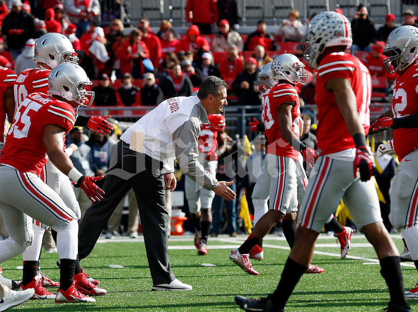 Ohio State Buckeyes head coach Urban Meyer runs players through drills prior to the NCAA football game against the Michigan Wolverines at Ohio Stadium on Nov. 29, 2014. The Buckeyes won 42-28. (Adam Cairns / The Columbus Dispatch)