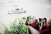 Two Buddhist monks take a picture of the Giant Buddha in Leshan, Sichuan, China, August  9, 2014.<br /> <br /> Smartphones are an essential tool of Chinese ordinary life. Everywhere in China, people use them to take pictures to share online, to talk and chat, to play videogames, to get access to the mainstream information, to get connected one each other. In the country where the main global social media are forbidden - Facebook, Twitter and Youtube are not available  -, local social networks such as WeChat have a wide spread all over the citizens. The effect is an ordinary and apparently compulsive way to get easy access to digital technology and modern way of communication. <br /> A life through the display. Yes, We Chat.<br /> <br /> © Giorgio Perottino