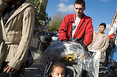 A father pushes his daughter in a buggy on Kilburn High Road, London.